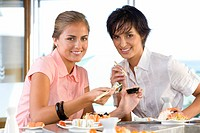 Two women eating in sushi bar, smiling, portrait