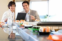 Couple with laptop in sushi bar, smiling, portrait