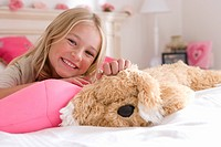 Girl 6-8 on bed with toy dog, smiling, portrait