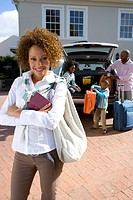 Woman in driveway with passports, family loading luggage into car in background, smiling, portrait