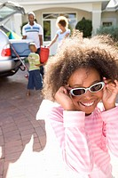 Girl 8-10 holding sunglasses to face in driveway, smiling