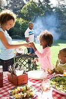 Family of four having picnic, father at barbeque, side view