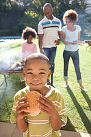 Boy 6-8 eating burger, family at barbeque in background, smiling, portrait
