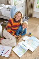 Mother and son 6-8 by books in bedroom, smiling, portrait, elevated view (thumbnail)