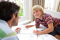 Boy 6-8 looking at book with father, smiling