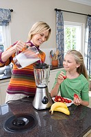 Mother and daughter 8-10 making banana and strawberry smoothie, smiling
