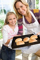 Mother and daughter 8-10 with oven tray of buns, smiling, portrait