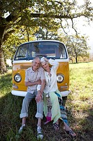 Senior couple sitting on front of camper van, smiling, portrait