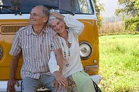 Senior couple sitting on front of camper van, holding hands, portrait of woman, close-up (thumbnail)