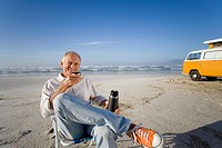 Senior man in chair on beach drinking from insulated flask, camper van in background, smiling, portrait