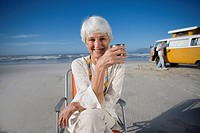 Senior woman in chair on beach with cup, camper van in background, smiling, portrait