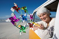 Senior woman holding pinwheel out window of camper van on beach, smiling, portrait