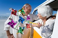 Senior man embracing woman with pinwheel through window of camper van on beach, smiling (thumbnail)