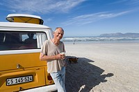 Senior man with cup leaning against camper van on beach, smiling, portrait