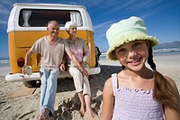 Girl 7-9 on beach by grandparents sitting on back of camper van, smiling, portrait