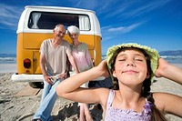 Girl 7-9 holding hat on head on beach by grandparents on back of camper van, smiling, close-up