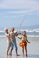 Girl 7-9 by grandparents fishing on beach, smiling, portrait (thumbnail)