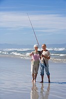 Senior couple with fishing rod on beach, smiling, portrait