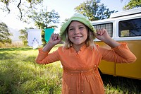 Girl 9-11 holding hat on head by camper van in field, smiling, close-up