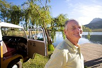Senior man by camper van by lake, smiling, portrait, close-up