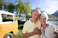 Senior couple arm in arm by lake and camper van, smiling, portrait