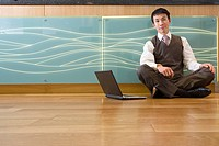 Businessman with legs crossed on floor by laptop computer, portrait, low angle view