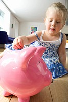 Girl 2-4 putting coin in piggy bank, low angle view (thumbnail)