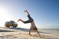 Boy 6-8 performing cartwheel on beach, camper van in background, low angle view