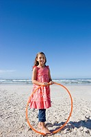 Girl 5-7 with plastic hoop on beach, smiling, portrait
