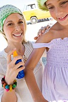 Mother applying sunscreen to daughter 5-7 on beach, smiling, low angle view