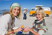 Family of four on beach, mother applying sunscreen to son 6-8, smiling, portrait