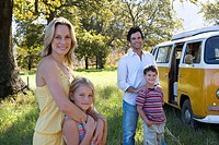 Mother embracing daughter 5-7 by father embracing son 6-8 in field by camper van, smiling, portrait