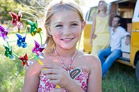 Girl 5-7 with pinwheel, parents by camper van in background, smiling