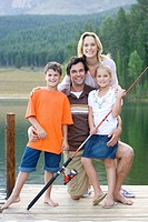 Family of four with fishing rod on jetty, smiling, portrait