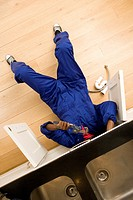 Plumber working under kitchen sink, overhead view (thumbnail)