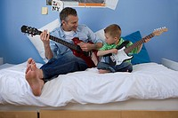 Father and son 2-4 on bed with electric guitars, looking at each other (thumbnail)
