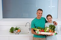 Couple in kitchen holding box of vegetables, smiling, portrait, elevated view