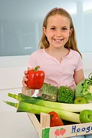 Girl 4-6 with box of vegetables on lap, smiling, portrait