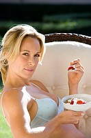 Young woman eating breakfast in underwear outdoors, portrait, close-up (thumbnail)