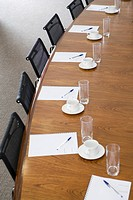 Close-up of notepads, pens, glasses and tea cups on conference room table
