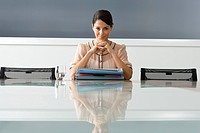 Businesswoman with files at boardroom table, smiling, portrait