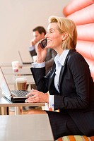 Businesswoman using mobile phone and laptop computer in cafe, smiling, side view