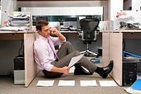 Businessman sitting on floor by piles of paperwork, using telephone, side view