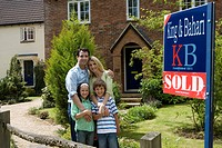 Family of four in front of house with 'sold' sign, smiling, portrait
