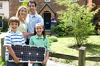 Family of four outside house, children 7-11 with solar panel, smiling, portrait