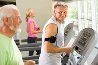 Mature man on treadmill smiling at senior man on treadmill
