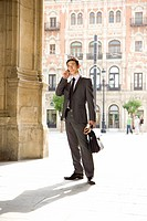 Businessman with briefcase and newspaper using mobile phone