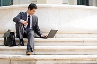 Businessman with briefcase using laptop computer on steps outdoors, low angle view