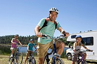 Family of four on bicycles by motor home, close-up of father, low angle view (thumbnail)