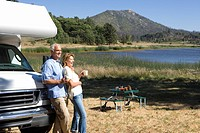 Mature couple with mugs by motor home by lake, side view (thumbnail)